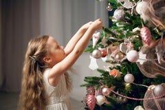 Menina bonito no vestido que decora a árvore de Natal fotos de stock royalty free
