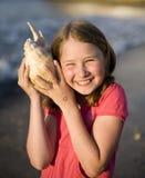 Menina bonito nova com a concha do mar no sorriso do seacoast Imagens de Stock Royalty Free