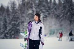 Menina bonito nova com snowboard foto de stock