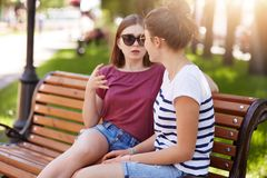 A menina bonito nova diz a seu amigo bonito leal a história velha assustador A menina alegre faz seu amigo acredita na história i foto de stock