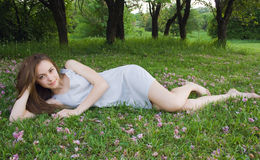 A menina bonito nova está inclinando-se na grama verde Imagem de Stock Royalty Free