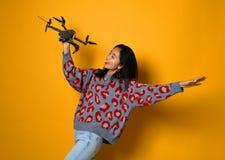 Menina bonito nova que guarda o quadcopter Criança que joga com zangão Educação, crianças, tecnologia, ciência, futuro e conceito fotografia de stock