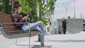 Menina bonito nova que texting em seu telefone em uma cidade filme