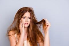 A menina bonito nova triste está olhando seu cabelo danificado com choque, s imagens de stock royalty free