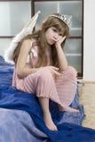 A menina bonito oito anos de anjo desgastando velho voa triste Foto de Stock
