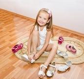 A menina bonito põe suas sapatas Imagens de Stock Royalty Free