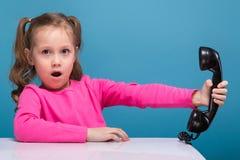 A menina bonito pequena atrativa na camisa cor-de-rosa com macaco e a calças azul guardam o cartaz vazio e as negociações um tele fotos de stock
