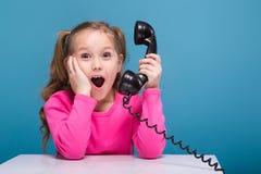 A menina bonito pequena atrativa na camisa cor-de-rosa com macaco e a calças azul guardam o cartaz vazio e as negociações um tele imagens de stock royalty free