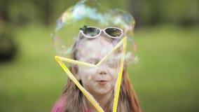 Menina bonito pequena brincalhão segura que funde o close-up médio do ventilador enorme da bolha de sabão do ar vídeos de arquivo