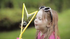 Menina bonito pequena brincalhão segura que funde o close-up médio do ventilador enorme da bolha de sabão do ar filme