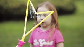 Menina bonito pequena brincalhão segura que funde o close-up médio do ventilador enorme da bolha de sabão do ar video estoque