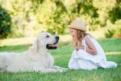 Menina bonito pequena da criança que joga com seu cão-pastor branco grande Foco seletivo Fotografia de Stock