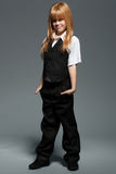 Menina bonito pequena do comprimento completo na camisa branca, na veste preta, na calças preta, isolada sobre o cinza foto de stock