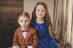 Menina bonito pequena do menino que abraça o jogo no fundo branco, o fim feliz da família acima do irmão e o sorriso da irmã Imagem de Stock