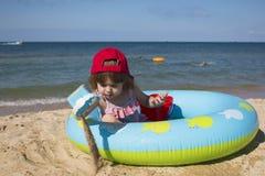A menina bonito pequena em um tampão vermelho senta-se em uma associação do ` s das crianças na praia Fotografia de Stock Royalty Free