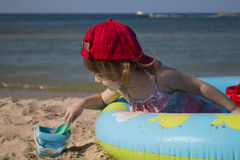 A menina bonito pequena em um tampão vermelho senta-se em uma associação do ` s das crianças na praia Foto de Stock Royalty Free