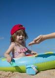 A menina bonito pequena em um tampão vermelho senta-se em uma associação e em jogos do ` s das crianças com sua mãe com areia Imagens de Stock