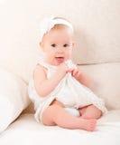 Menina bonito pequena em um vestido branco e com sorriso da flor fotografia de stock royalty free