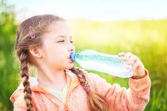 A menina bonito pequena na natureza bebe a água imagem de stock