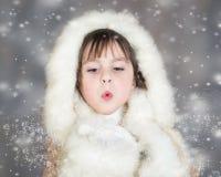 A menina bonito pequena no fundo do inverno funde a neve Imagem de Stock