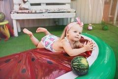 Menina bonito pequena nos macacões e um lenço cor-de-rosa que encontra-se em um colchão inflável sob a forma das fatias de melanc imagem de stock royalty free