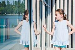 A menina bonito pequena olha seu dia ensolarado da reflexão imagens de stock royalty free