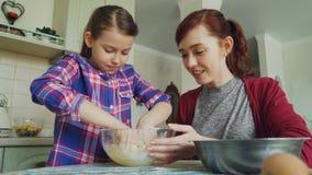 Menina bonito pequena que ajuda sua mãe na cozinha que agita a massa para cookies na bacia A mamã e a filha têm o divertimento vídeos de arquivo