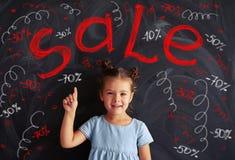 Menina bonito pequena que aponta com seu dedo nas inscrição o do giz Fotografia de Stock Royalty Free