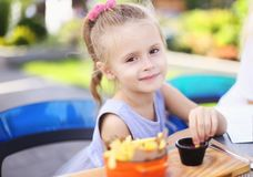 Menina bonito pequena que come fritadas do rench com molho no café da rua fora imagem de stock royalty free