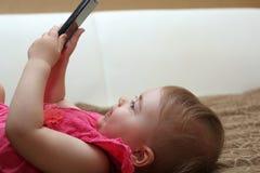 Menina bonito pequena que encontra-se no sofá e que joga com um smartphone Imagens de Stock