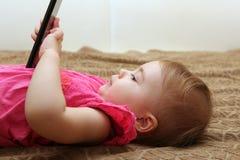 Menina bonito pequena que encontra-se no sofá e que joga com um smartphone Fotografia de Stock