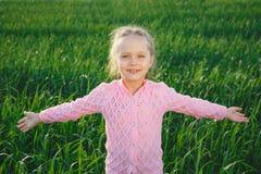 Menina bonito pequena que está no dia verde da luz do sol do prado imagens de stock royalty free