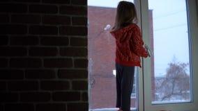 Menina bonito pequena que está no peitoril da janela, olhando para fora em uma arquitetura da cidade nevado filme