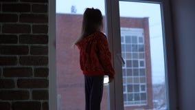 Menina bonito pequena que está no peitoril da janela, olhando para fora em uma arquitetura da cidade nevado vídeos de arquivo