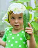 Menina bonito pequena que guarda um pepino em sua mão Imagens de Stock