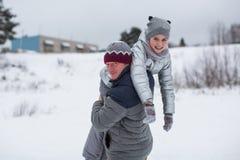 Menina bonito pequena que joga com o pai no inverno fora Divertimento fotografia de stock royalty free