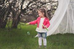 Menina bonito pequena que joga no jardim luxúria fotos de stock royalty free