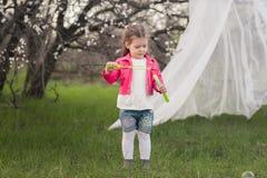 Menina bonito pequena que joga no jardim luxúria fotografia de stock