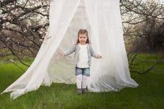 Menina bonito pequena que joga no jardim luxúria imagem de stock