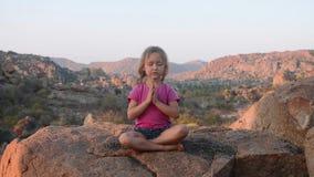 Menina bonito pequena que medita sobre a montanha video estoque