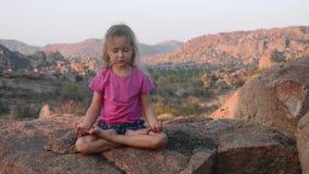 Menina bonito pequena que medita sobre a montanha filme