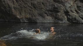 Menina bonito pequena que salta na água do lago da montanha a sua mãe vídeos de arquivo