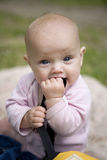 Menina bonito pequena que senta-se na grama no parque. imagem de stock