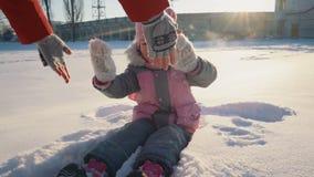 Menina bonito pequena que senta-se na neve e no sorriso filme