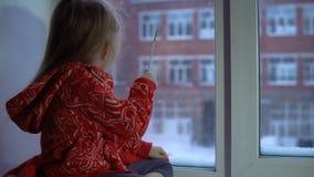 Menina bonito pequena que senta-se no peitoril da janela, olhando para fora em uma arquitetura da cidade nevado video estoque