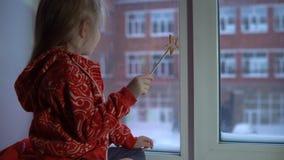 Menina bonito pequena que senta-se no peitoril da janela, olhando para fora em uma arquitetura da cidade nevado filme