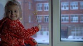 Menina bonito pequena que senta-se no peitoril da janela, olhando para fora em uma arquitetura da cidade nevado vídeos de arquivo
