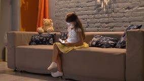 Menina bonito pequena que senta-se no sofá e que datilografa na tabuleta, fundo moderno da sala de visitas, dentro vídeos de arquivo