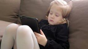 Menina bonito pequena que senta-se no sofá e que joga com tabuleta video estoque