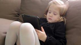 Menina bonito pequena que senta-se no sofá e que joga com tabuleta vídeos de arquivo